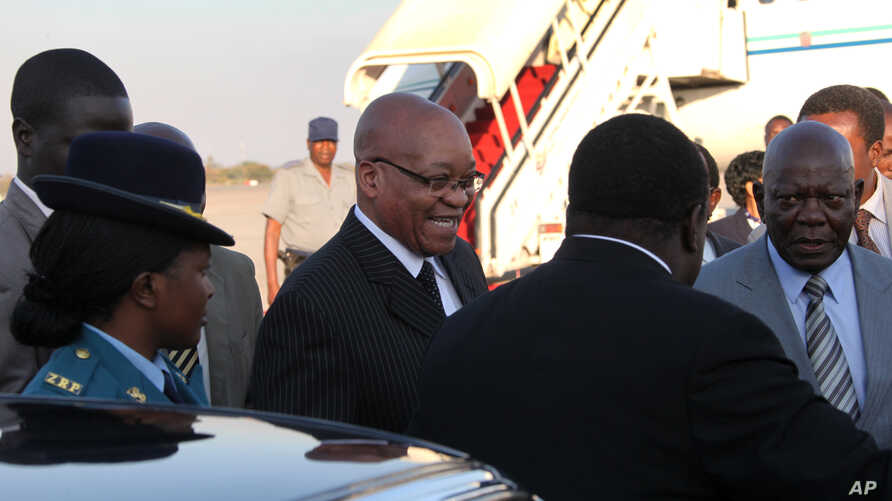 South African President Jacob Zuma, center, is greeted upon arrival in Harare, Zimbabwe, August 15, 2012.