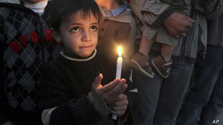 A Palestinian boy holds a candle during a protest in the northern Gaza Strip to mark the second anniversary of Israel's three-week offensive in Gaza, 27 Dec 2010.
