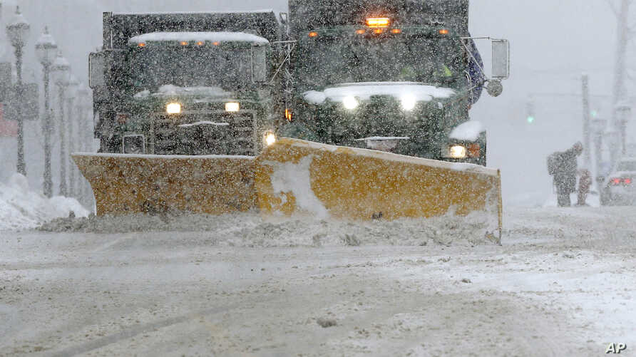 FILE - Snow plows clear a street during a snowstorm, Feb. 12, 2017, in Waltham, Mass.