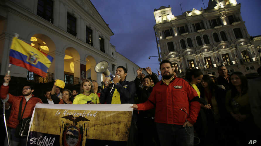 """FILE - Protesters demand the government remove Julian Assange's Ecuadorean nationality, carrying a sign that reads in Spanish """"Nationality is earned, not given away,"""" outside the government palace in Quito, Ecuador, Oct. 31, 2018."""