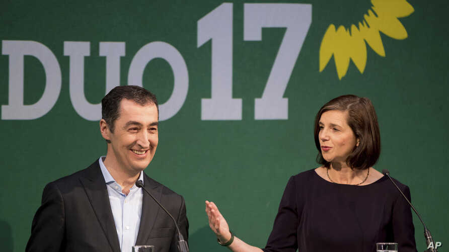 Cem Ozdemir, party chairman of German Greens, and parliamentary faction leader Katrin Goering-Eckardt, right, ask question during a news conference in Berlin, Wednesday, Jan. 18, 2017 after they have been elected as the party's top candidates in the