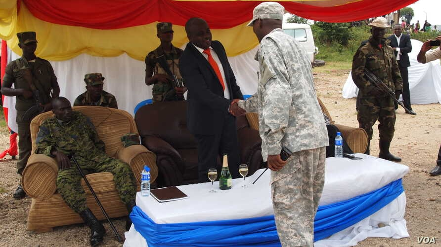 New president of the M23 rebel movement, Bertrand Bisimwa (in orange tie) shakes hands with M23 military commander Sultani Makenga, in Bunagana in eastern DRC, March 7, 2013. (N. Long/VOA)