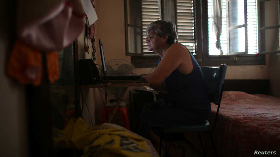Retired teacher Margarita Marquez, 67, uses the internet after it was recently installed at her home in old Havana, Cuba, Dec. 29, 2016.