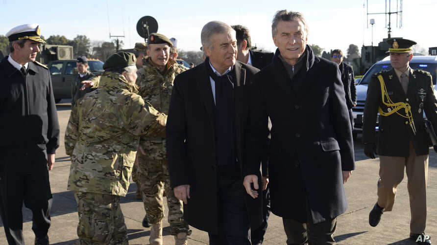 In this photo released by Argentina's presidential press office, Argentina's President Mauricio Macri, front right, walks with Defense Minister Oscar Raul Aguad at a military headquarters on the outskirts of Buenos Aires, Argentina, July 23, 2018.