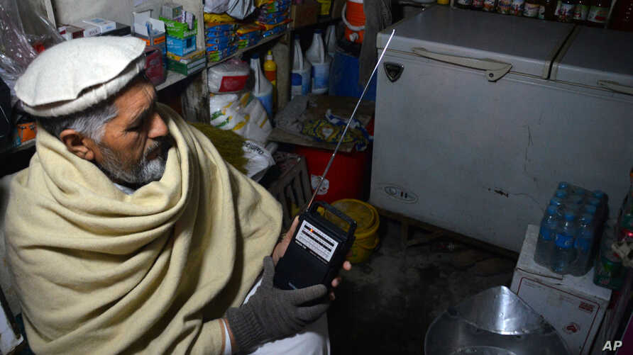 FILE - An Afghan shopkeeper listens to Islamic State Radio at his shop in Jalalabad, capital of Nangarhar province, Afghanistan, Jan. 10, 2016.