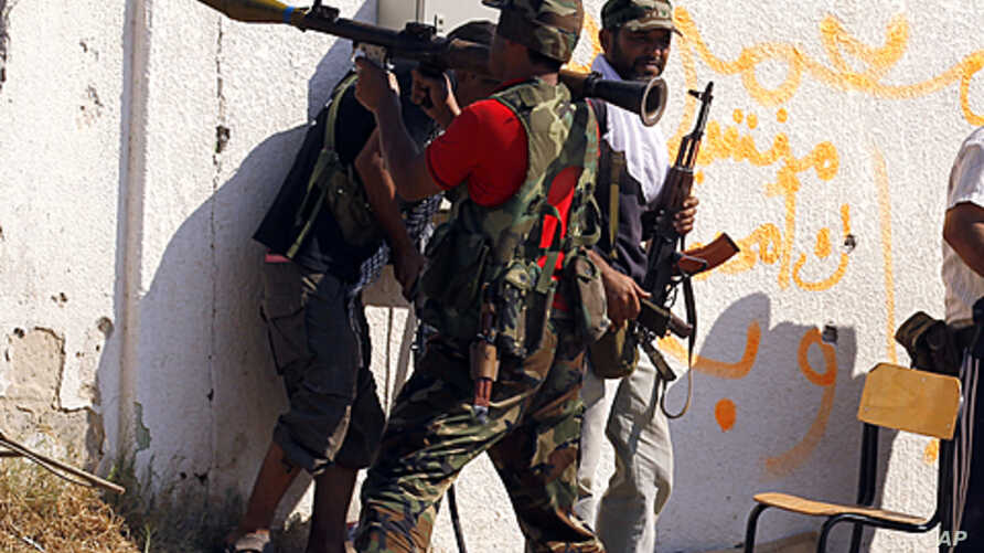 A Libyan rebel fighter prepares to fire a rocket propelled grenade launcher towards a sniper position as they make a final push to flush out pro-Gaddafi forces from the Bab al Aziziya compound in Tripoli, August 24, 2011