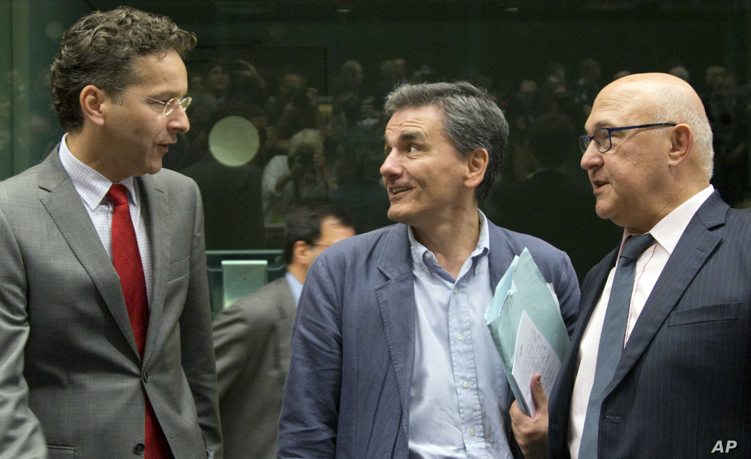 FILE - Greek Finance Minister Euclid Tsakalotos, center, speaks with Dutch Finance Minister Jeroen Dijsselbloem, left, and French Finance Minister Michel Sapin during a meeting of eurozone finance ministers in Brussels, July 7, 2015.