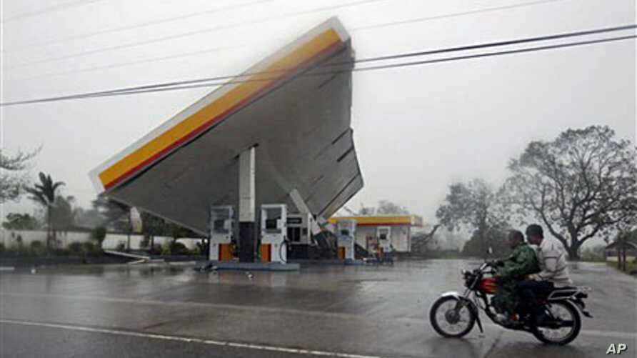 """Motorists drive past a filling station which was toppled by typhoon Megi (local name """"Juan""""), 18 Oct 2010, at Cauayan, Isabela province, northeastern Philippines"""