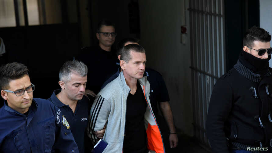 Alexander Vinnik, a Russian suspected of running a money laundering operation using bitcoin, is escorted by police officers while leaving a court in Thessaloniki, Greece, October 11, 2017.