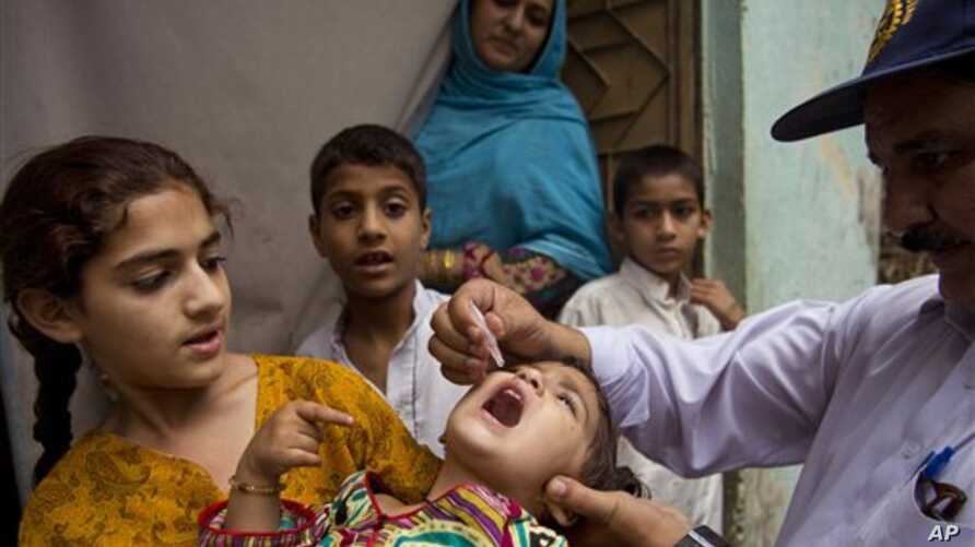 A Pakistani health worker gives a polio vaccine to a child in Rawalpindi, Pakistan, Tuesday, May 6, 2014. Pakistan's health minister says the country is taking extra ordinary measures to meet the new situation it is going to face after polio travel r