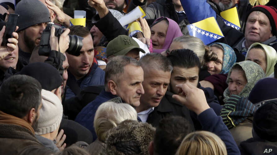 Former Bosnian Army commander of Srebrenica Naser Oric, center, escorted as he leaves court in Sarajevo, Bosnia, Friday, Nov. 30, 2018. A Bosnian appeals court has acquitted the wartime commander of Srebrenica who was accused of committing atrocities