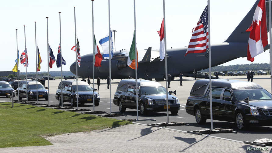 The convoy of hearses with the remains of the victims of Malaysia Airlines MH17 drives past international flags as it leaves Eindhoven airport to a military base in Hilversum, July 23, 2014.