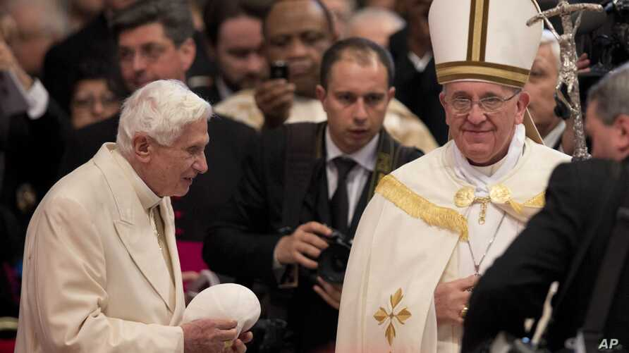 Pope Francis, right,  salutes Pope Emeritus Benedict XVI at the end of a consistory inside the St. Peter's Basilica at the Vatican, Feb.22, 2014.