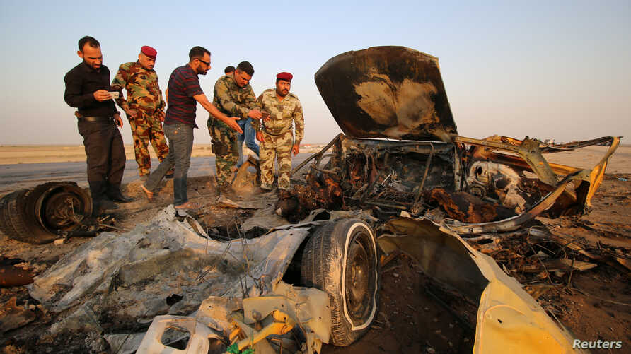FILE - Iraqi security forces inspect the site of a bomb attack at a police checkpoint on a highway near the southern Iraqi city of Nassiriya, Sept. 14, 2017.