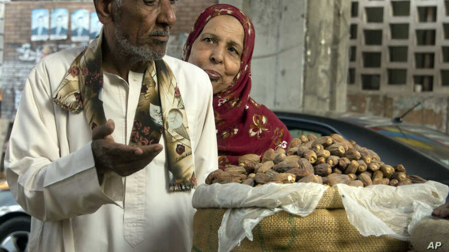 A man argues with his wife as they buy dried dates to break their fast at the date market in Cairo, Egypt, during the holy month of Ramadan, June 2, 2017.