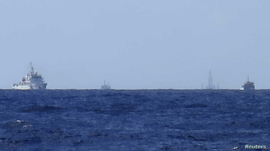 Chinese ships are seen on the horizon guarding the Haiyang Shiyou 981, known in Vietnam as HD-981, oil rig (2nd R) in the South China Sea, July 15, 2014.