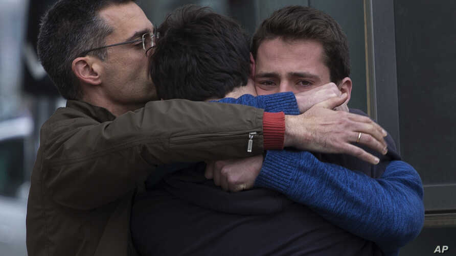 Family members of people involved in a crashed plane comfort each other as they arrive at the Barcelona airport in Spain, March 24, 2015.