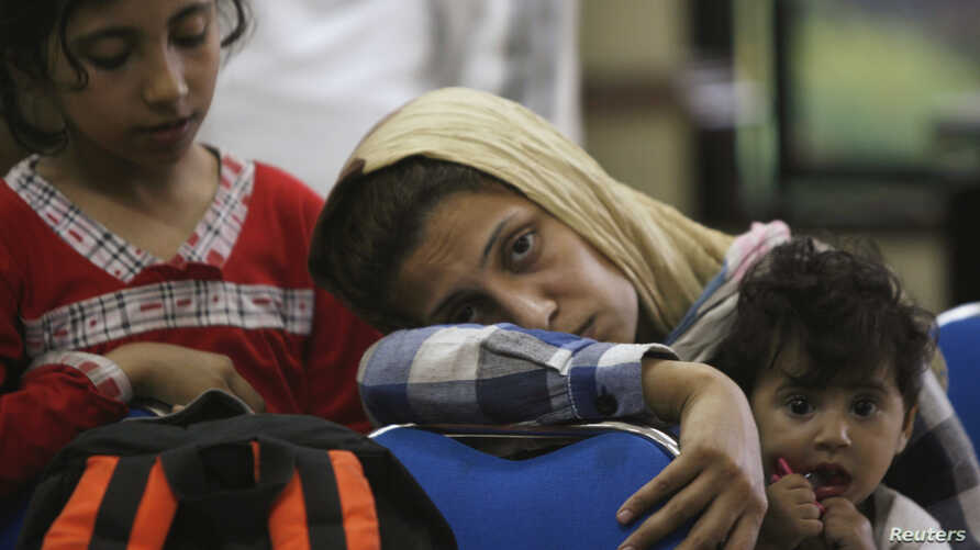 Asylum seekers hoping to reach Australia, wait in a police station in Surabaya , East Java province July 29, 2012.