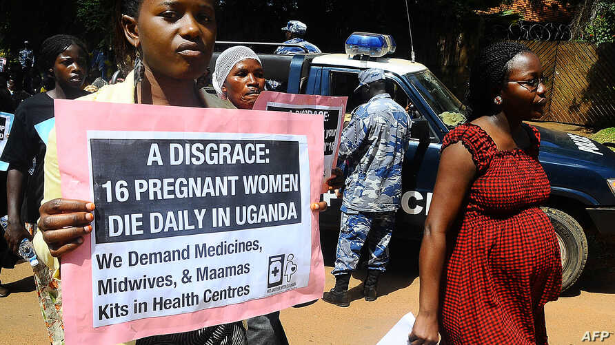 Activists carry placards outside the Constitutional court during a peaceful march in the capital Kampla to protest the delay by a Ugandan court to deliver a ruling in a landmark lawsuit regarding the cases of two women who unattended bled to death wh
