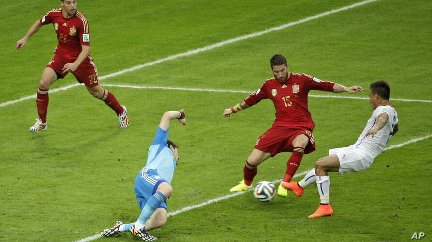 Chile's Eduardo Vargas (R) iin white, scores the opening goal during the group B World Cup soccer match between Spain and Chile at the Maracana Stadium in Rio de Janeiro, Brazil, June 18, 2014.