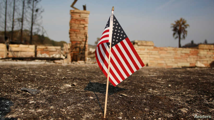FILE - An American flag stands in front of a home destroyed after a wildfire tore through Santa Rosa, Calif., Oct. 15, 2017.