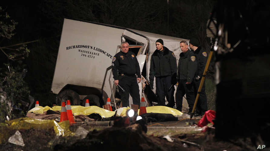 Investigators examine body bags of victims near the scene where at least eight people were killed and 38 people were injured after a tour bus carrying a group from Tijuana, Mexico crashed with two other vehicles near Yucaipa, California, February 3,