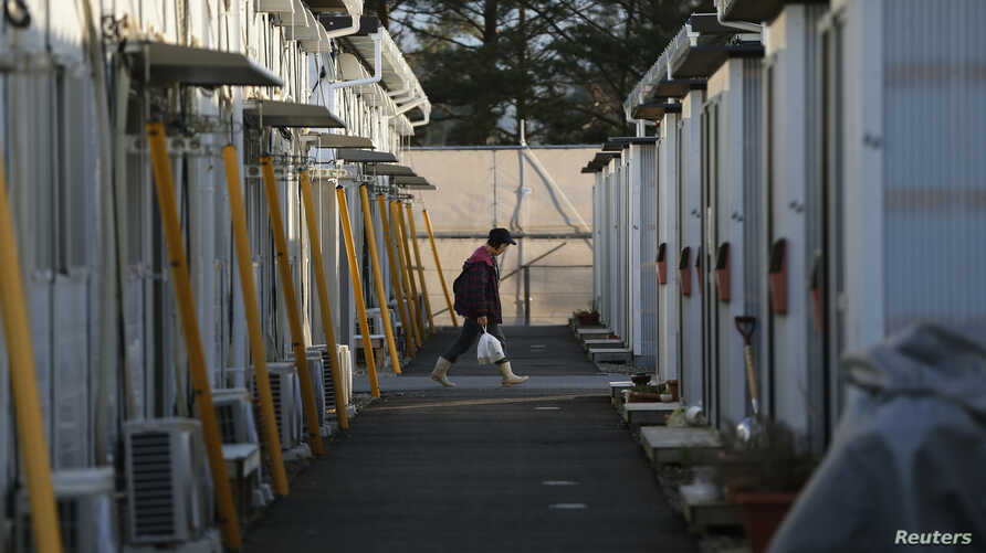 A woman walks in a temporary housing complex where evacuees from the Miyakoji area of Tamura are living, at Funahiki area in Tamura, Fukushima prefecture, April 1, 2014.