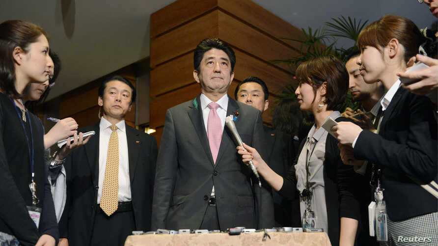Japan's Prime Minister Shinzo Abe (C) speaks to media after a meeting with cabinet ministers at his official residence in Tokyo, in this photo taken by Kyodo, Apr. 12, 2013.