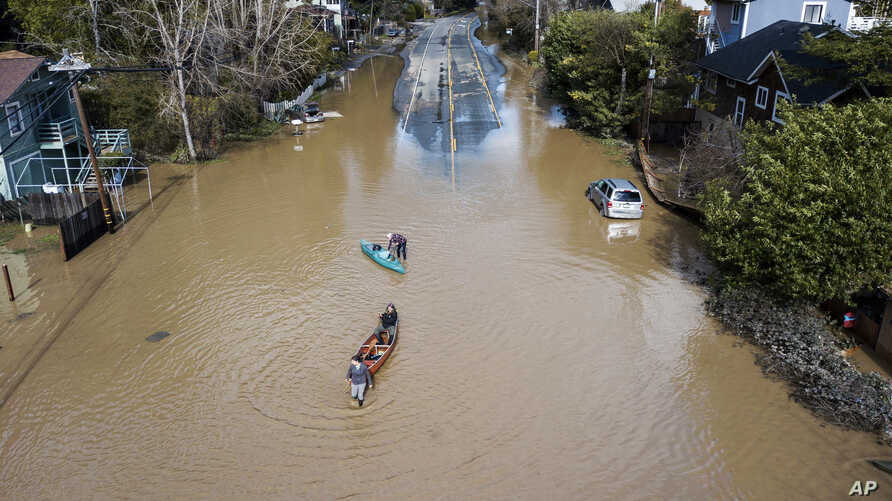 FILE - People take their boats into the water on the flooded River Road in Guerneville, Calif., Feb. 28, 2019.
