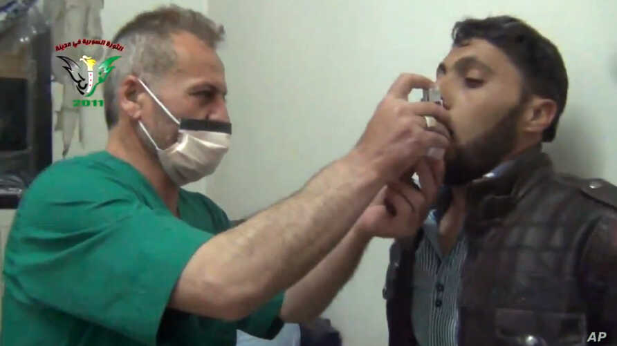 FILE - This video image from an anti-Bashar Assad activist group shows a Syrian man being treated with an inhaler in Kfar Zeita, north of Damascus, after what witnesses said was a chlorine gas attack, April 18, 2014.