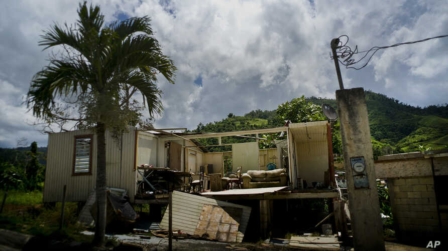FILE - In this Sept. 8, 2018 file photo, a home that was abandoned after Hurricane Maria hit one year ago stands full of furniture in the San Lorenzo neighborhood of Morovis, Puerto Rico.