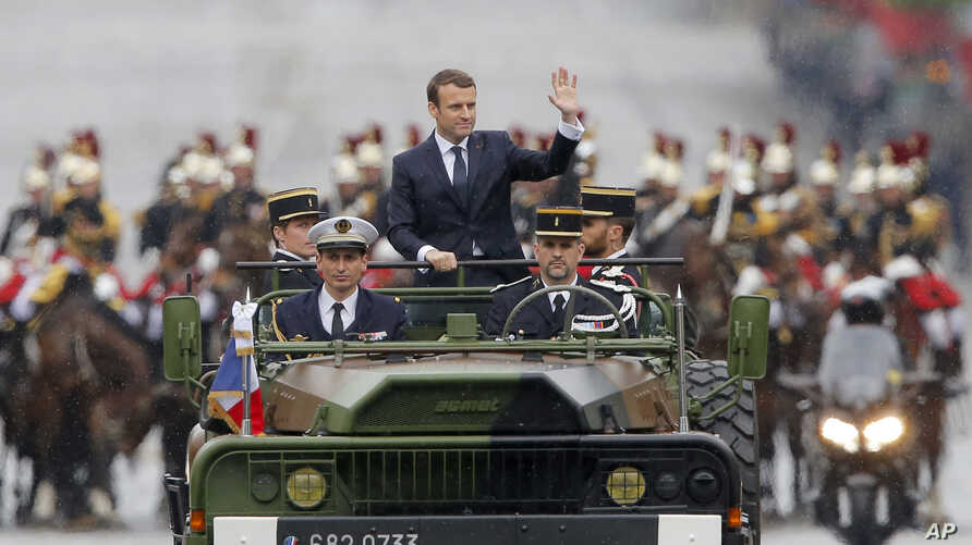 New French President Emmanuel Macron waves from a military vehicle as he rides on the Champs Elysees avenue towards the Arc de Triomphe in Paris, May 14, 2017.