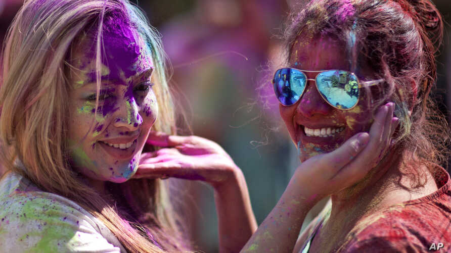 A foreign tourist, left and an Indian smear colored powder on each other as they celebrate Holi, the festival of colors in Hyderabad, India, March 12, 2017.