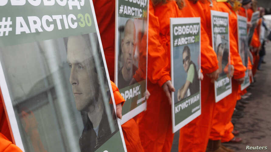 FILE - Greenpeace activists hold portraits of those detained on the boat Arctic Sunrise during a rally in Moscow, Russia.