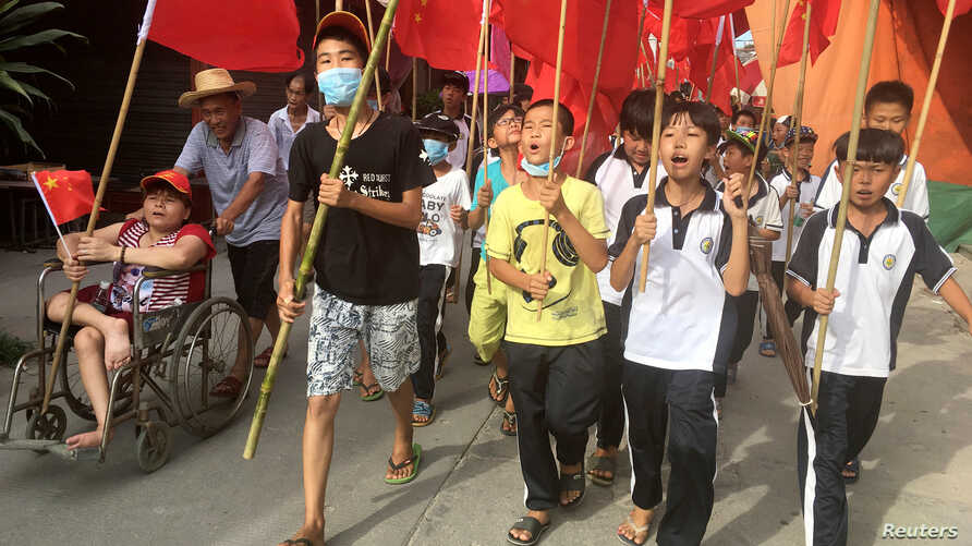 Villagers including schoolchildren take part in a protest march, demanding the release of their village chief Lin Zuluan, in Wukan, in China's Guangdong province, June 21, 2016.