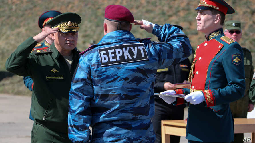"""A photo provided by the Russian Defense Ministry shows Russian Defense Minister Sergei Shoigu (L) awarding a former Ukrainian special forces """"Berkut"""" officer (back to camera) at a military base in Sevastopol, Crimea, March 24, 2014."""