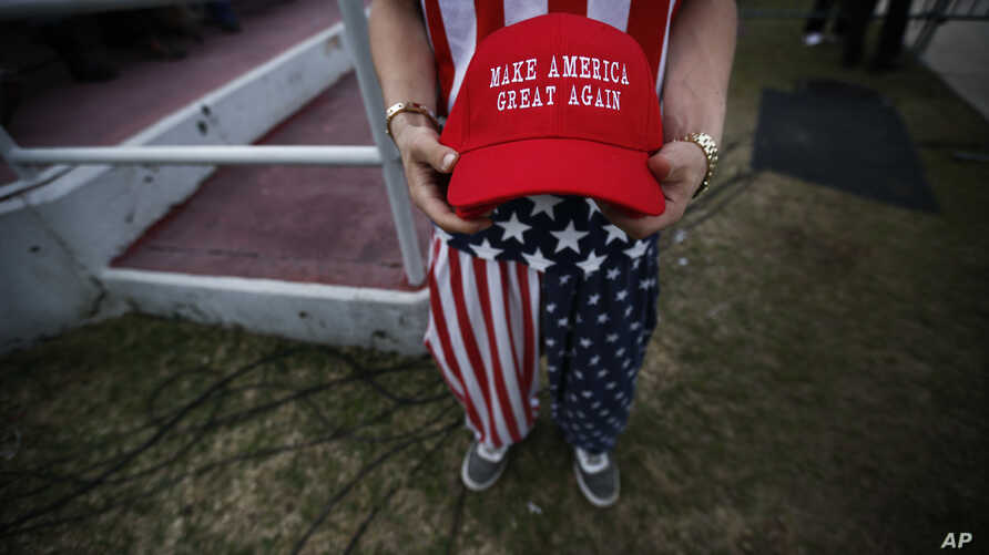 "A man dressed in American flag clothes holds ""Make America Great Again"" hats before a campaign rally at the Ladd–Peebles Stadium,  Dec. 17, 2016, in Mobile, Alabama. Comedians the world over thrive on slogans and this one has not remained unscathed."