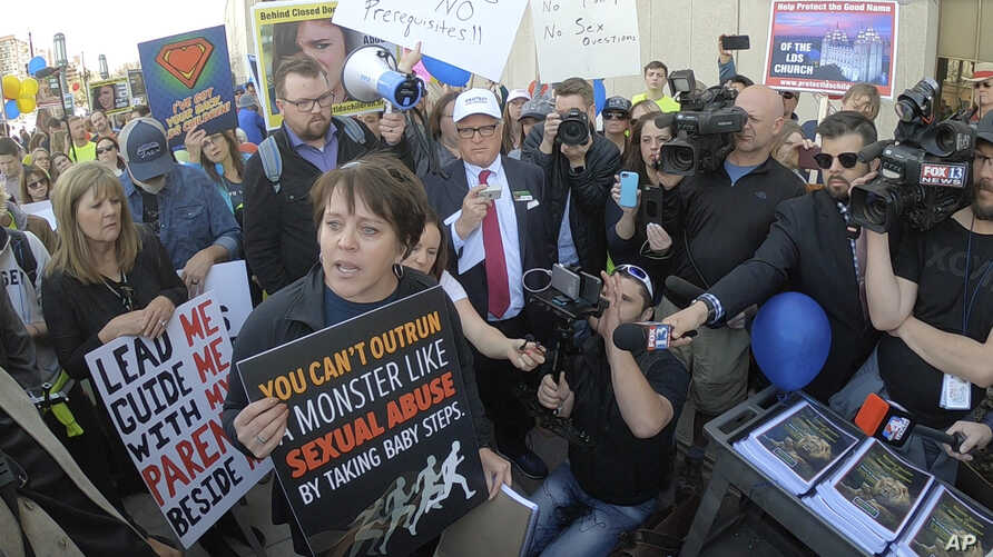 Sue Krupa and about 1,000 Mormons and former Mormons march to the church's headquarters in Salt Lake City, March 30, 2018, to deliver petitions demanding an end to one-on-one interviews between Mormon youth and lay leaders and the sexual questions th