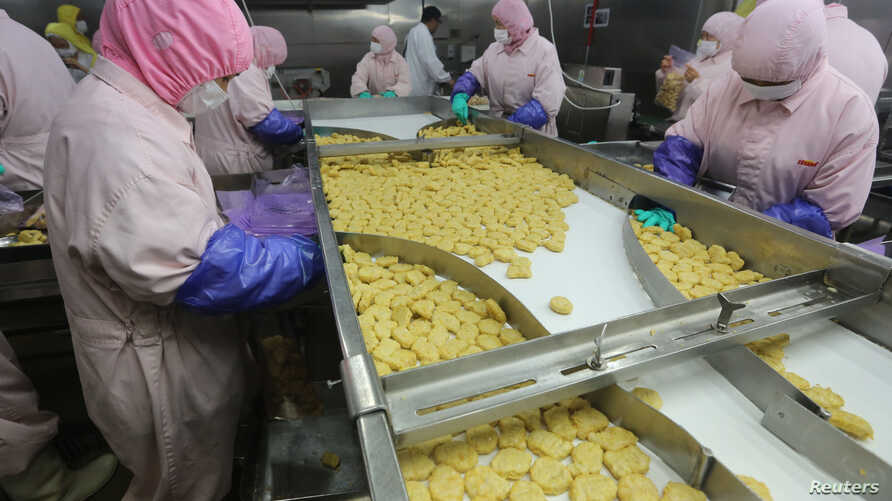 Employees work at a production line prior to a seizure conducted by officers from the Shanghai Food and Drug Administration, at the Husi Food factory in Shanghai, July 20, 2014.