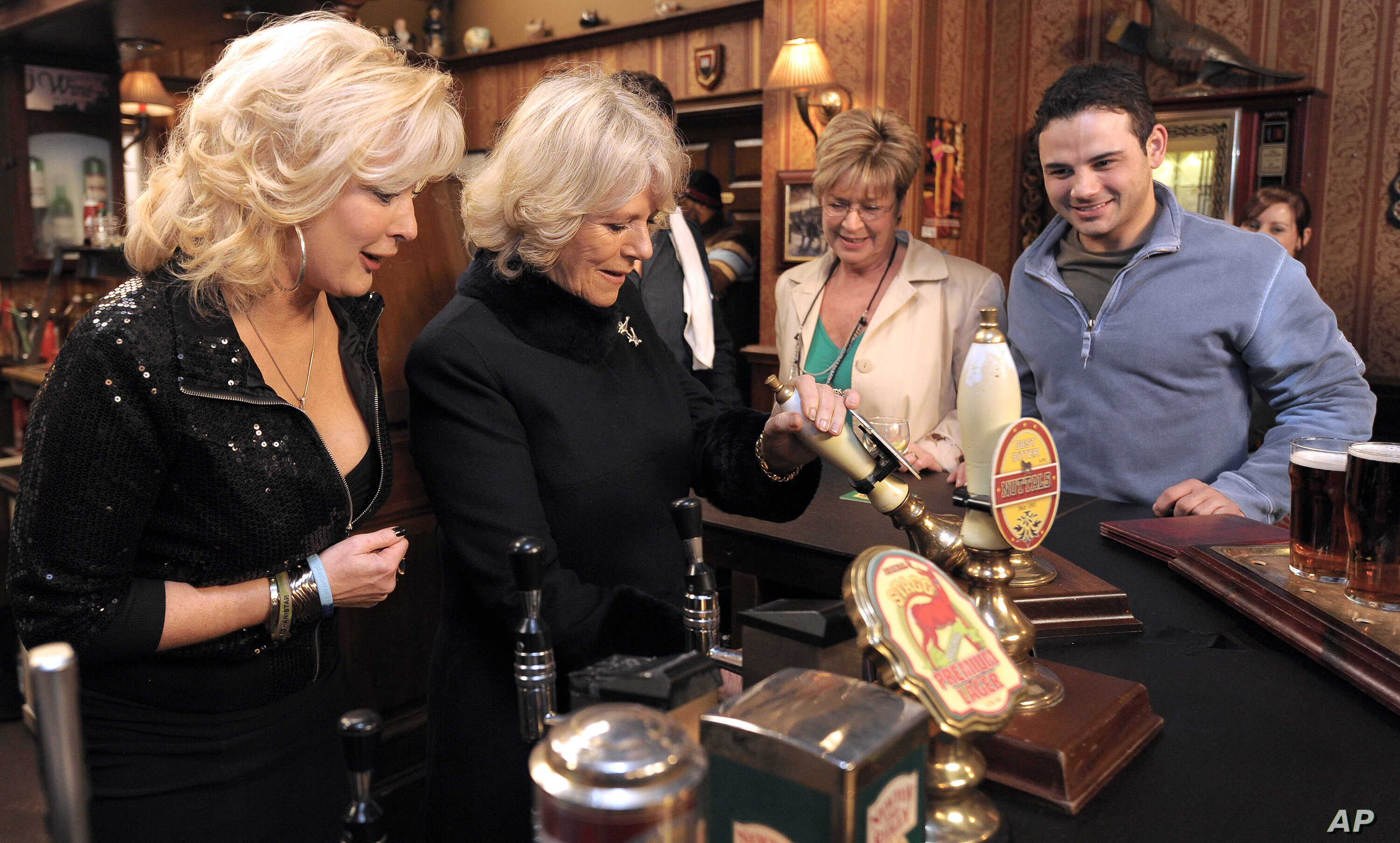 FILE - In this Thursday, Feb. 4, 2010 file photo, the Duchess of Cornwall, second left, pulls a pint of beer in the Rovers Return pub, as she meets actors Beverley Callard, left, who plays landlady Liz McDonald, Anne Kirkbride, second right, who play