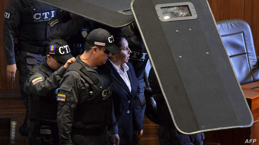 Former director of the Colombian Security Department (DAS) Maria del Pilar Hurtado (C) arrives under custody at the Supreme Court for the reading of her sentence for espionage in Bogota, April 30, 2015.