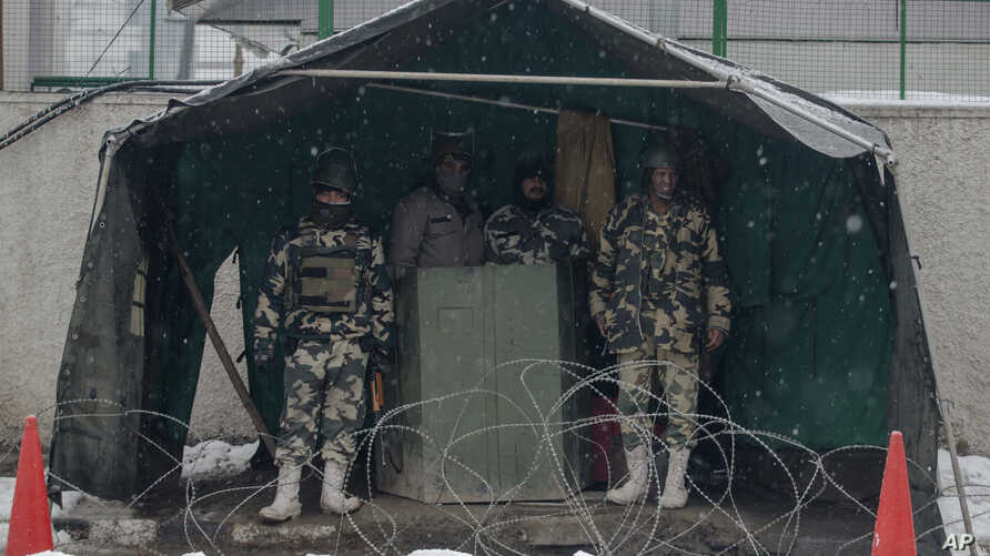 Indian paramilitary soldiers take shelter from snow as they stand guard in Srinagar, Indian controlled Kashmir, Jan. 25, 2017. Four members of a family and an Indian soldier were killed Wednesday when they were buried by two separate avalanches in t