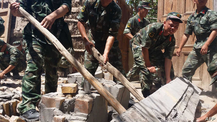 Rescuers help villagers dismantle damaged walls after a shallow 6.4-magnitude earthquake hit the area in Pishan county in Hetian, northeast China's Xinjiang region, July 3, 2015.