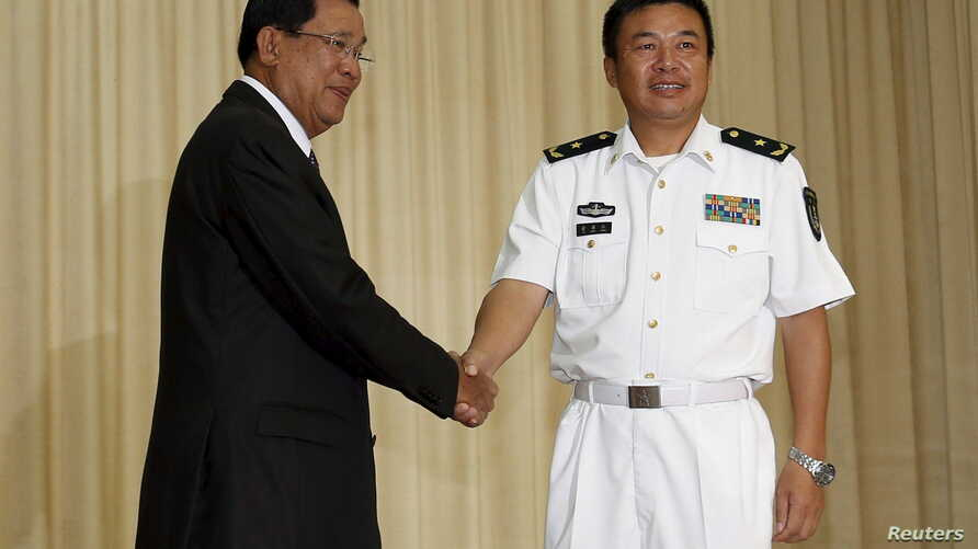 Yu Manjiang (R), commander officer of the Chinese fleet, is welcome by Cambodia's Prime Minister Hun Sen in Phnom Penh, February 24, 2016