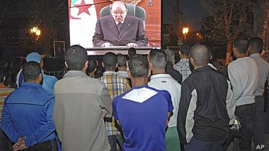 People listen to the speech of Algeria's President Abdelaziz Bouteflika on a giant television screen in Algiers, April 15, 2011
