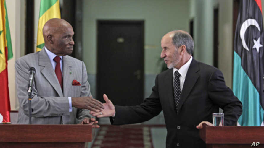 Senegal's President Abdoulaye Wade, left, shakes hands with National Transitional Council chairman Mustafa Abdul-Jalil after their joint press conference in Benghazi, Libya, June 9, 2011