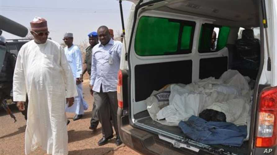 Ibrahim Gaidam, Governor of Yobe state, left,  looks at  bodies of students  inside an ambulance outside a mosque in Damaturu,  Nigeria,  Tuesday, Feb. 25, 2014. Islamic militants killed dozens of students in a pre-dawn attack Tuesday on a northeast