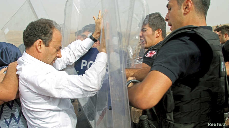 A parliamentarian from the pro-Kurdish Peoples' Democratic Party, Osman Baydemir (L), scuffles with riot police as he walks with his party members to the southeastern town of Cizre, near Idil in Sirnak province, Turkey, Sept. 10, 2015.