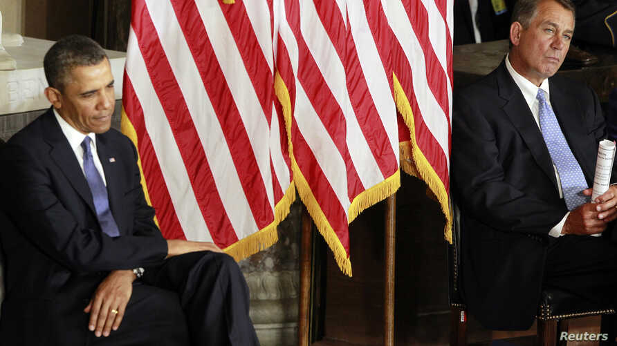 U.S. President Barack Obama (L) sits alongside House Speaker John Boehner during the unveiling of a statue in honor of civil rights activist Rosa Parks, in Statuary Hall in the U.S. Capitol in Washington, February 27, 2013.