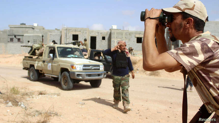 A fighter from forces aligned with Libya's new unity government monitors Islamic State locations at Algharbiyat area in Sirte, June 21, 2016.